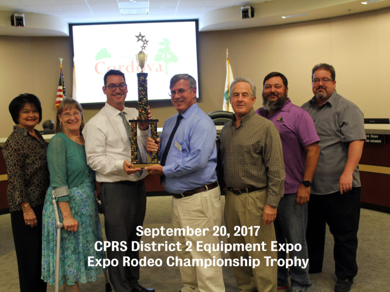 CRPD staff posing with board members and district administrator while holding a trophy won for staff competing in CPRS District 2 Equipment Expo Rodeo
