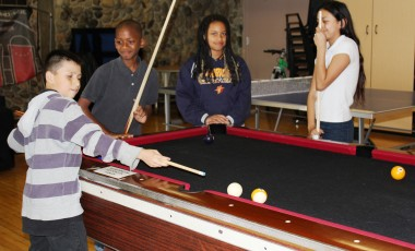 Teens playing pool in the HYDE Out Teen Center