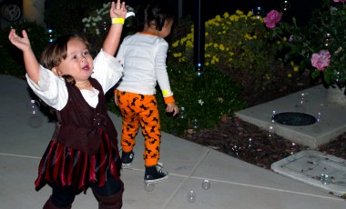 little girl dressed as a pirate playing with bubbles
