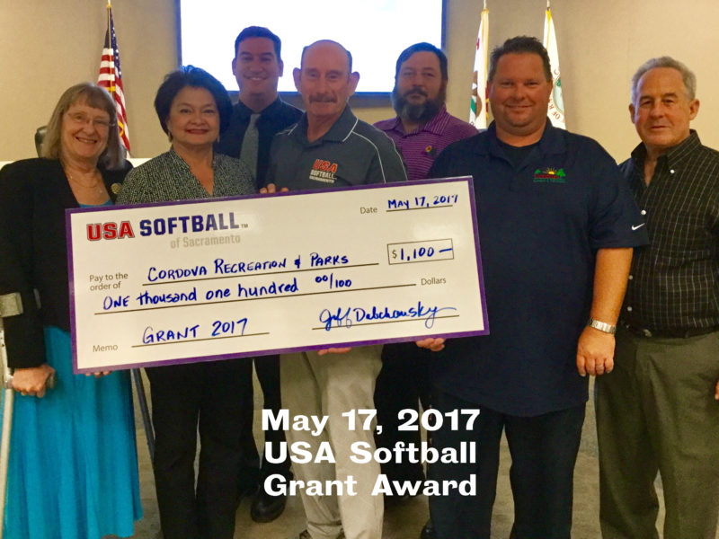 Board of directors accepting grant from USA Softball