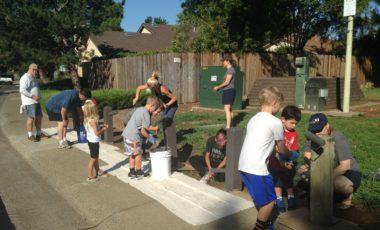 Volunteers sanding bollards at Sunriver Park as part of an enhancement program
