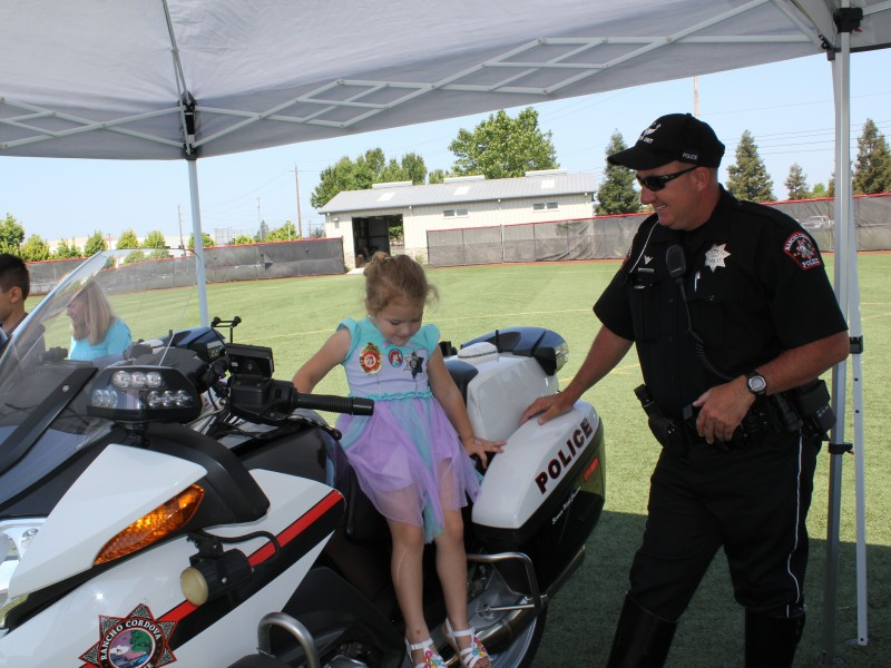 Child getting on a police motorcycle at Meet the Machines
