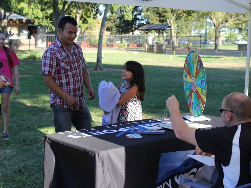 Adults interacting with vendors at Party in the Park event