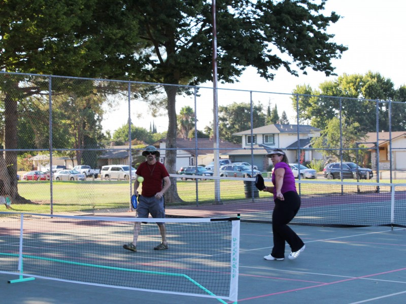 Adults playing tennis